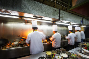 35685625 - crowded kitchen, a narrow aisle, working chef.